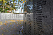 Among autumn leaves are the names of fallen WW2 Polish air crew at the Polish War Memorial, on 6th November 2019, in South Ruislip, Northolt, London, England. The Polish War Memorial is in memory of airmen from Poland who served in the Royal Air Force as part of the Polish contribution to World War II. The memorial was designed by Mieczyslaw Lubelski, who had been interned in a forced labour camp during the war. It is constructed from Portland stone with bronze lettering and a bronze eagle, the symbol of the Polish Air Force. The original intention was to record the names of all those Polish airmen who lost their lives while serving during WW2 (a total of 2,408) but there was not enough space for this and, as a compromise, the names of the 1,241 who died in operational sorties are there instead.