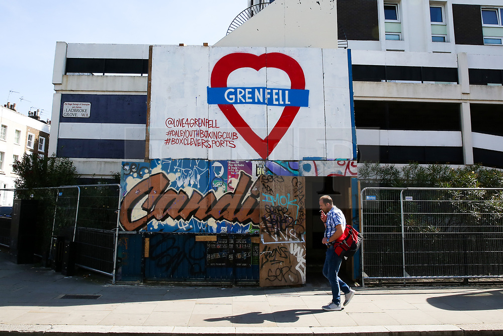 © Licensed to London News Pictures. 22/08/2019. London, UK. A man walks past a residential property which has been boarded up with a large Grenfell sign ahead of the 2019 Notting Hill Carnival in West London, which takes place this bank holiday weekend. Up to 1 million people are expected to attend the biggest street party in Europe. Photo credit: Dinendra Haria/LNP