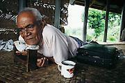 An elderly family member of the Lagavales cannot walk well anymore and spends most of his day lounging on the hand woven mats on the floor of his house. Western Samoa. The Lagavale family lives in a 720-square-foot tin-roofed open-air house with a detached cookhouse in Poutasi Village, Western Samoa. The Lagavales have pigs, chickens, a few calves, fruit trees and a vegetable garden. Material World Project.