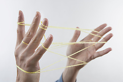 Close-up of a man's hands making a cats cradle with string, Bavaria, Germany