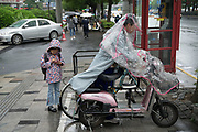 Mother and child in rain with electric motorbike and telephone