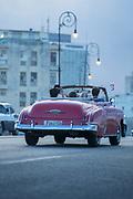 Vintage car on Malecon city street under storm clouds, Havana, Cuba