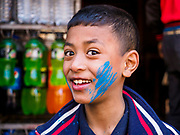 12 MARCH 2017 - BHAKTAPUR, NEPAL:  A boy with blue powder on his cheek at a Holi celebration in Bhaktapur. Holi, a Hindu religious festival, has become popular with non-Hindus in many parts of South Asia, as well as people of other communities outside Asia. The festival signifies the victory of good over evil, the arrival of spring, end of winter, and for many a festive day to meet others. Holi celebrations in Nepal are not as wild as they are in India.    PHOTO BY JACK KURTZ