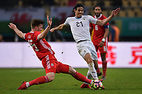 """Edinson Cavani, right, of Uruguay national football team kicks the ball to make a pass against Lee Evans of Wales national football team in their final match during the 2018 Gree China Cup International Football Championship in Nanning city, south China's Guangxi Zhuang Autonomous Region, 26 March 2018.<br /> <br /> Edinson Cavani's goal in the second half helped Uruguay beat Wales to claim the title of the second edition of China Cup International Football Championship here on Monday (26 March 2018). """"It was a tough match. I'm very satisfied with the result and I think that we can even get better if we didn't suffer from jet lag or injuries. I think the result was very satisfactory,"""" said Uruguay coach Oscar Tabarez. Wales were buoyed by a 6-0 victory over China while Uruguay were fresh from a 2-0 win over the Czech Republic. Uruguay almost took a dream start just 3 minutes into the game as Luis Suarez's shot on Nahitan Nandez cross smacked the upright. Uruguay were dealt a blow on 8 minutes when Jose Gimenez was injured in a challenge and was replaced by Sebastian Coates. Inter Milan's midfielder Matias Vecino of Uruguay also fired at the edge of box from a looped pass but only saw his attempt whistle past the post. Suarez squandered a golden opportunity on 32 minutes when Ashley Williams's wayward backpass sent him clear, but the Barca hitman rattled the woodwork again with goalkeeper Wayne Hennessey well beaten."""