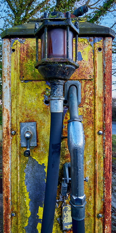 Rusty and paint peeling old petrol pumps at a long since closed and abandoned derilict roadside garage and petrol station at Steeple Ashton Wiltshire UK.