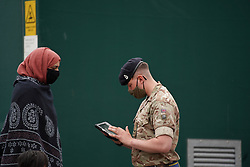 © Licensed to London News Pictures. 29/05/2021. Bolton,UK. Members of the public speak to Royal Horse Artillery at a temporary Covid-19 vaccination centre at Eden Boys' school in Halliwell, Bolton. Bolton has the highest Covid-19 infection rate in the country as the Indian variant of Covid-19 continues to spread.  Photo credit: Ioannis Alexopoulos/LNP