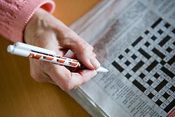 Older woman's hand doing a newspaper crossword,