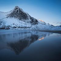 Winter mountain reflection on Bunes beach, Moskenesøy, Lofoten Islands, Norway