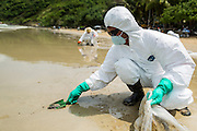 02 AUGUST 2013 - KOH SAMET, RAYONG, THAILAND:  Workers use trowels to scoop oil contaminated sands on Ao Prao beach on Koh Samet island. About 50,000 liters of crude oil poured out of a pipeline in the Gulf of Thailand over the weekend authorities said. The oil made landfall on the white sand beaches of Ao Prao, on Koh Samet, a popular tourist destination in Rayong province about 2.5 hours southeast of Bangkok. Workers from PTT Global, owner of the pipeline, up to 500 Thai military personnel and volunteers are cleaning up the beaches. Tourists staying near the spill, which fouled Ao Prao beach, were evacuated to hotels on the east side of the island, which was not impacted by the spill. Officials have not said when Ao Prao beach would reopen. PTT Global Chemical Pcl is part of state-controlled PTT Pcl, Thailand's biggest energy firm.   PHOTO BY JACK KURTZ