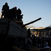 KIEV, UKRAINE - February 20, 2014: Anti-government protestors unload a truck full of tree trunks, to be used as a reinforce of defensive barricades in a access road to the parliament buildings in central Kiev. Hours earlier, riot police responded to an advance by protestors, with gunfire that, according to the opposition, killed at least 70 and as many as 100 people. The drastic escalation of the three-month-old Ukraine crisis left the country reeling from the most lethal violence in decades. CREDIT: Paulo Nunes dos Santos