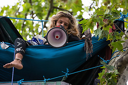 Tree protector 'Athena' from HS2 Rebellion, an umbrella campaign group comprising longstanding campaigners against the HS2 high-speed rail link as well as Extinction Rebellion activists, addresses a protest rally in Parliament Square on 4 September 2020 in London, United Kingdom. The rally, and a later protest action at the Department of Transport during which activists glued themselves to the doors and pavement outside and sprayed fake blood around the entrance, coincided with an announcement by HS2 Ltd that construction of the controversial £106bn high-speed rail link will now commence.