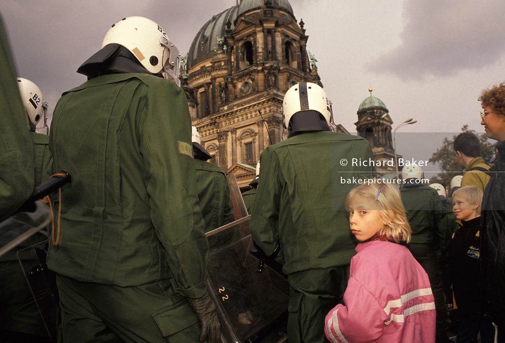 A year after the fall of the Berlin Wall and the end of the Communist Eastern Bloc era, riot police tower over a young German girl outside Berlin Cathedral, on 4th November 1990, in Berlin, Germany.