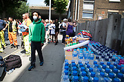 Donations of food, water, clothing and toiletries are collected at a make shift help / drop off point following a blaze at Grenfell Tower near Notting Hill on 14th June 2017 in West London, United Kingdom. The huge fire engulfed the tower block, trapping many people in their homes. A number of fatalities are reported. The block of flats in the Borough of Kensington and Chelsea, billowed large plumes of smoke way above the capital after the blaze broke out in the early hours of Wednesday morning. Londoners came out on the streets to help, offer food and water, support and assistance to those who had lost their homes or didn't know the whereabouts of their friends and family.