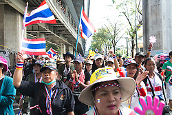 © Licensed to London News Pictures. 05/01/2014. Anti-Goverment protestors march down one of Bangkok's main road during the third day of the 'Bangkok Shutdown' as anti-government protesters continue with their 'shutdown' of Bangkok.  Major intersections in the heart of the city have been blocked in their campaign to oust Prime Minister Yingluck Shinawatra and her government in Bangkok, Thailand. Photo credit : Asanka Brendon Ratnayake/LNP