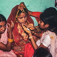A young brides's family and friends help prep her for at a traditional Bengali wedding in Dhaka, Bangladesh, 1977.