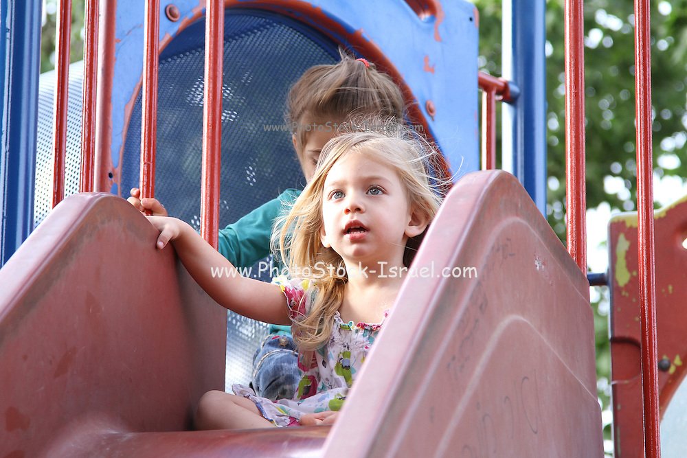 Young girl of three in a playground on a slide