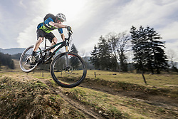 Mountain biker performing jump on bicycle on single track, Bavaria, Germany