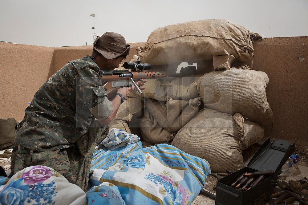 © Licensed to London News Pictures. 28/09/2014. Al-Yarubiyah, Syria. Using a home made 14.5mm rifle, a sniper belonging to Syrian Kurdish YPG forces in Al-Yarubiyah, Syria, fires at Islamic State positions across the border in Rabia, Iraq.<br /> <br /> Facing each other across the Iraq-Syria border, the towns of Al-Yarubiyah, Syria, and Rabia, Iraq, were taken by Islamic State insurgents in August 2014. Since then The town of Al-Yarubiyah and parts of Rabia have been re-taken by fighters from the Syrian Kurdish YPG. At present the situation in the towns is static, but with large exchanges of sniper and heavy machine gun fire as well as mortars and rocket propelled grenades, recently occasional close quarter fighting has taken place as either side tests the defences of the other. Photo credit: Matt Cetti-Roberts/LNP