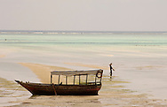 An old wooden boat in the sea at low tide. Paje, Zanzibar, Tanzania