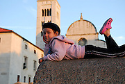 Child (5 years old), lounging on wall, Church of St. Mary (Crkva Sveti Marije) in background, in late afternoon sunlight. Zadar, Croatia