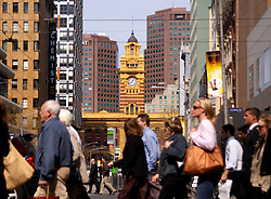 Many people crossing street in central district of Melbourne with historic Flinders Railway station to rear in Australia