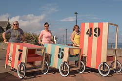 Community arts event Art Walk Porty got underway this afternoon with a promenade procession of the event's 'Art Carts'. The carts, designed to echo the old style bathing carts that used to grace Portobello beach, will be used in a variety of ways by different artists at locations across Portobello, Edinburgh's seaside suburb. The Art Walk is now in its third year and will run over the next day days with a range of events and exhibitions.  Pictured: Artists Rosy Naylor, Jill Martin Boualaxai and Jenny Martin.<br /> <br /> <br /> <br /> © Jon Davey/ EEm