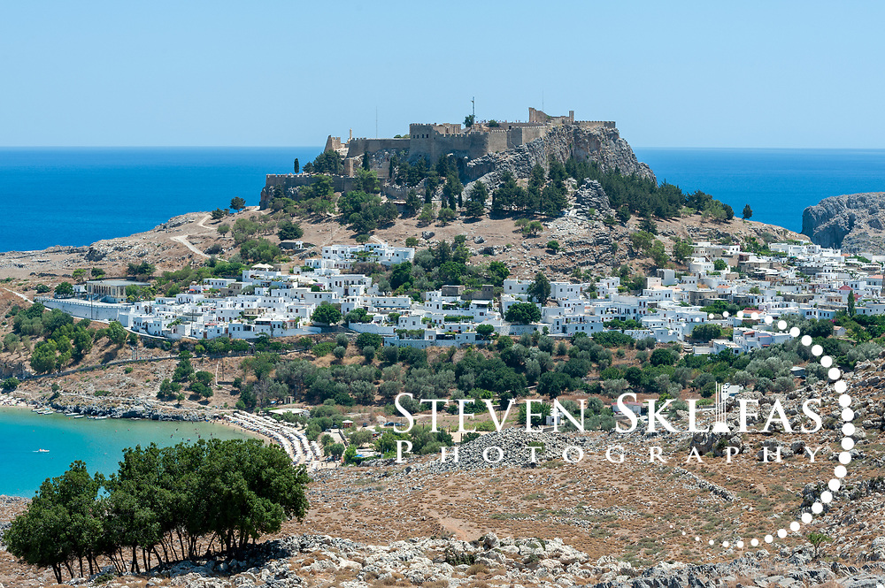 Rhodes. Greece. Panoramic view of the picturesque and magnetic town of Lindos which is a dazzling labyrinth of whitewashed house and alleyways that climb the slopes to the dramatic ancient Acropolis and Crusader Knights castle. Lindos is located on the east coast of the island of Rhodes which is the largest of the Dodecanese Island group and one of the most popular Greek Islands.
