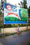 A vietnamese woman rides a bicycle and crosses an environmental campaign against plastic bags. Hoi An, Vietnam, Asia 2012.