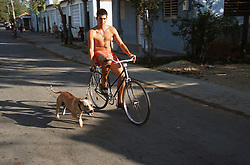 Man riding a bicycle through Vinales; Pinar Province; Cuba; with a dog on a lead,