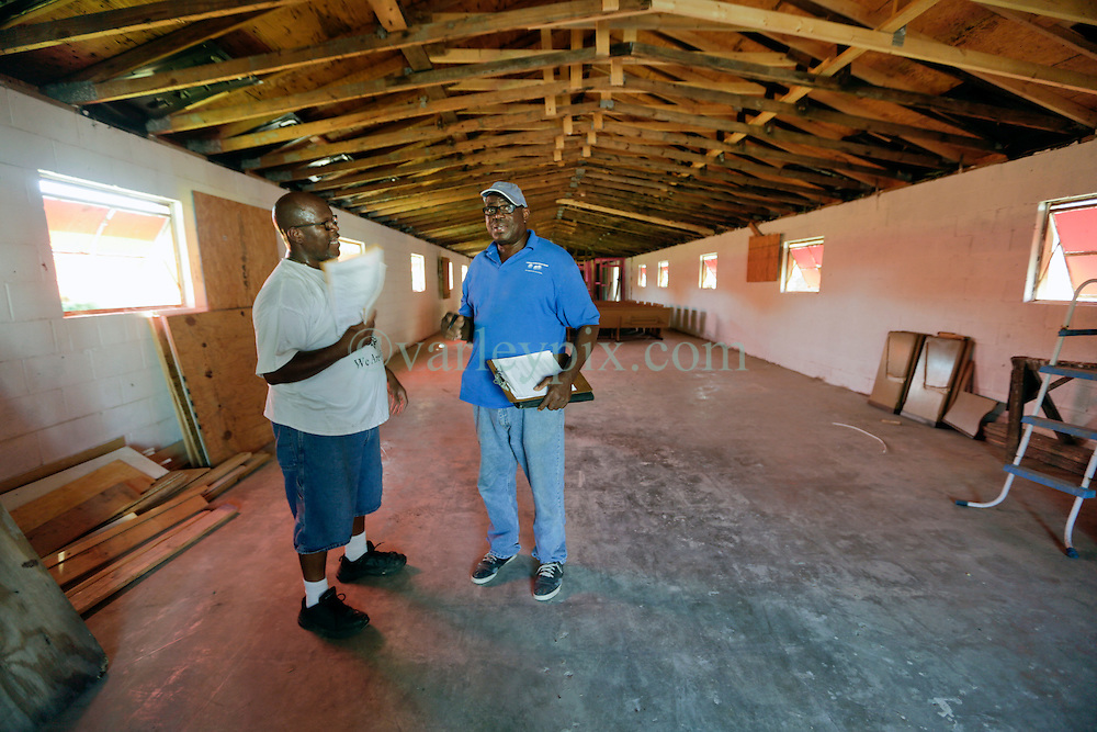 26 August 2015. New Orleans, Louisiana. <br /> Hurricane Katrina revisited. <br /> Disciples of Christ Christian Fellowship Ministry. <br /> L/R; Pastor Darrell Turner and contractor Larry Knight of the Freedom Development Group go over plans for the church. The pastor and his congregants are rebuilding a decade after Katrina shuttered the doors.<br /> Photo credit©; Charlie Varley/varleypix.com.