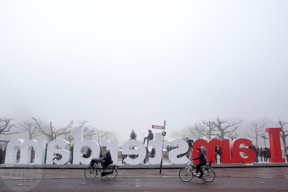 In Amsterdam fietsen twee vrouwen langs de tekst I Amsterdam op het Museumplein in de mist.<br /> <br /> In Amsterdam two women cycling along the text I Amsterdam on the Museumplein in the fog.