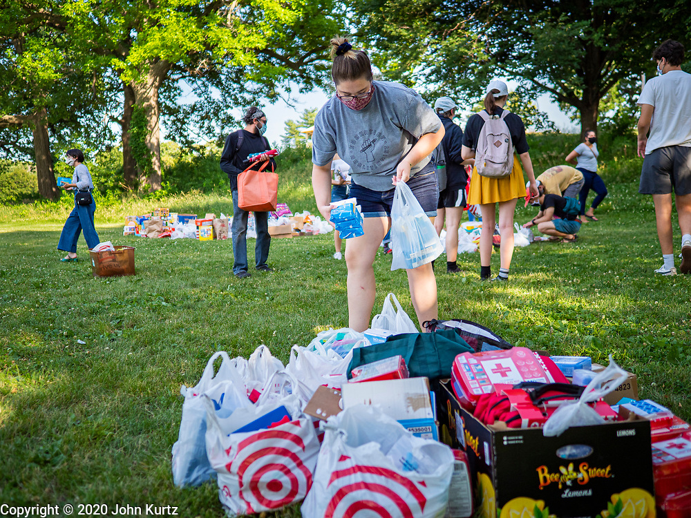 25 JUNE 2020 - DES MOINES, IOWA: A Black Lives Matter supporter sorts first aid supplies for the homeless donated to BLM. Nearly 100 volunteers came to a community support event organized by Black Lives Matter in Good Park in Des Moines. They sorted supplies donated to BLM, including food, sanitary supplies, first aid supplies, batteries, blankets, tents, and bottled water. The emergency packages will be distributed to homeless people in Des Moines.        PHOTO BY JACK KURTZ