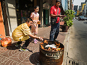 """07 FEBRUARY 2016 - BANGKOK, THAILAND: People burn """"ghost money"""" to make merit for Chinese New Year in Bangkok's Chinatown. Chinese New Year, also called Lunar New Year or Tet (in Vietnamese communities) starts Monday February 8. The coming year will be the """"Year of the Monkey."""" Thailand has the largest overseas Chinese population in the world; about 14 percent of Thais are of Chinese ancestry and some Chinese holidays, especially Chinese New Year, are widely celebrated in Thailand.        PHOTO BY JACK KURTZ"""