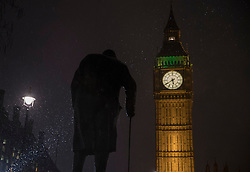 © Licensed to London News Pictures. 12/01/2017. London, UK. Snow flurries are illuminated by spoltlights on a statue of Winston Churchill in Parliament Square in sight of Big Ben. Rain and heavy snow are expected to hit most of the UK today. Photo credit: Peter Macdiarmid/LNP