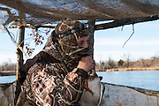 Tony Troxell bites the head of a wounded mallard duck to kill it while hunting at a private watershed lake in Shamrock, Oklahoma