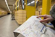 A woman holds a public transportation map in an U-bahn station in Berlin, Germany, April 09, 2012.