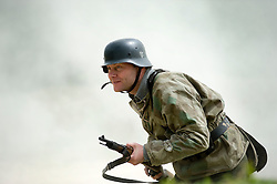 Reenactor from Northern World War Two Association, dressed as a member of the elite Gross Deutschland division moves forward through smoke during a private 24hr excerise, held at Sutton Grange, near Ripon in Yorkshire. He is wearing the Iconic German Steel Helmet (Stahlhelm) with Splinterpatern Camouflage clothing and crrying a Mauser K98 Kar Rifle<br />