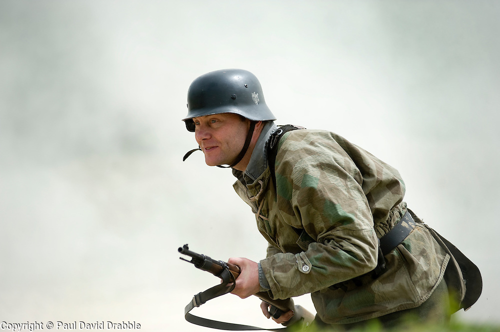 Reenactor from Northern World War Two Association, dressed as a member of the elite Gross Deutschland division moves forward through smoke during a private 24hr excerise, held at Sutton Grange, near Ripon in Yorkshire. He is wearing the Iconic German Steel Helmet (Stahlhelm) with Splinterpatern Camouflage clothing and crrying a Mauser K98 Kar Rifle<br />  15  May 2010 .Images © Paul David Drabble.