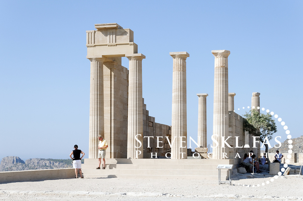 Rhodes. Greece. View on a dazzling summer's morning of the partially restored 4th century BC Temple of Lindian Athena which crowns the ancient acropolis of Lindos. The temple was one of the most famous sites of the ancient world, visited by Alexander the Great and offers great views of the Aegean Sea and coastline.