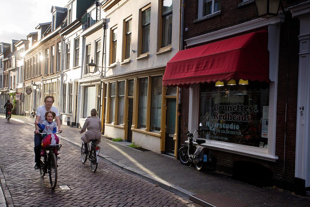 In Utrecht fietst een vader met zijn zoontje op het kinderzitje voorop door de Haverstraat.<br /> <br /> In Utrecht a father cycles with his son in a child seat at the front of the bike at the Haverstraat.