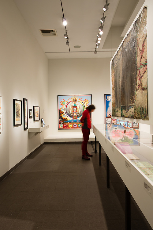 """A gallery in The American Folk Art Museum, with Paul Laffoley's """"Alchemy: the telenomic process of the Universe"""" on the back wall."""