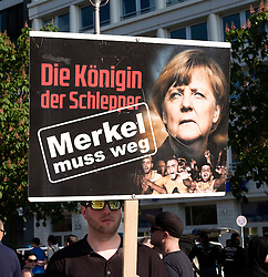 "Far-right demonstrators protest against Islam, refugees and Angela Merkel in Berlin. Sign sign, ""The Queen of the traffickers - Merkel must go""."