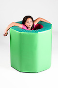 Indoor playground  Young girl in a foam rubber barrel On white Background