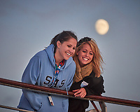 Happy Students out on Deck for Sunset with the Waxing Gibbous Moon in the Background.Image taken with a Nikon D800 camera and 70-300 mm VR lens.