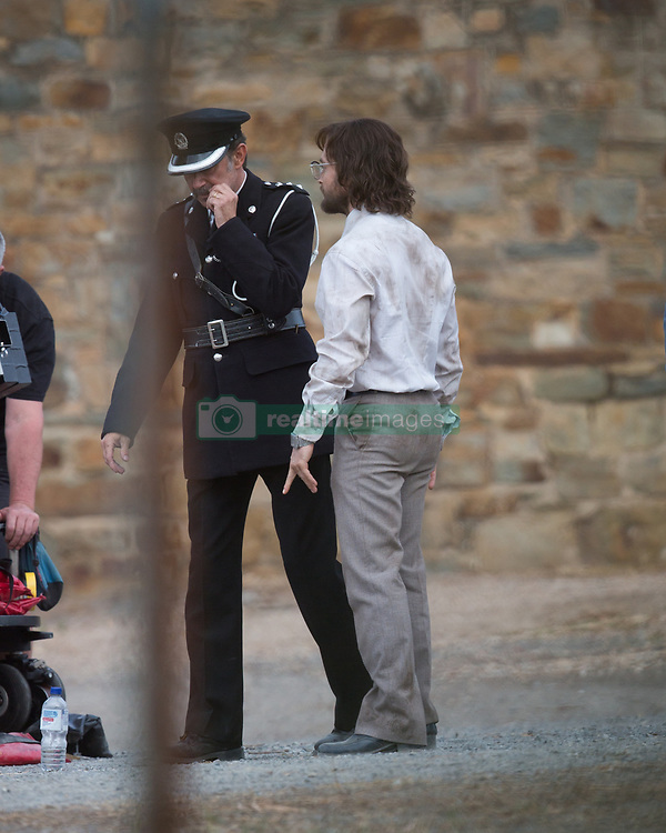 """EXCLUSIVE: Daniel Radcliffe was looking worse for wear as he got into character for filming of """"Escape from Pretoria"""" in Adelaide. Daniel was looking scruffy as he wore a very dirty business shirt tucked into his pants with a tie and grey pants with a pair of eye glasses. His co-star had a bloodied face. The filming took place at the old Adelaide Gaol which has been transformed into Pretoria prison for filming. Daniel and his co-star in the scene were shackled as they exited a white van and were met by many officers. Daniel's character had his legs shackled as well as his hands in parts of the scene. It's a far different look from the boy who was once Harry Potter. Filming will continue over the next few weeks in Adelaide. 11 Mar 2019 Pictured: Daniel Radcliffe. Photo credit: MEGA TheMegaAgency.com +1 888 505 6342"""