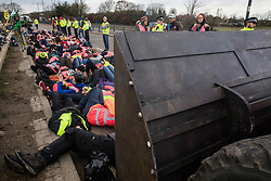 London, UK. 8 December, 2019. Climate activists from Extinction Rebellion stage a lie-in in front of a full-scale mock-up of a bulldozer outside Heathrow airport during a Bikes Against Bulldozers protest against Heathrow expansion and the greenwashing of climate commitments by political parties. The protest took the form of a Critical Mass bicycle ride from Hyde Park followed by the lie-in to which Boris Johnson and John McDonnell were invited in order to fulfil their pledge of lying down in front of bulldozers to be used for Heathrow expansion.