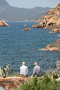 Two senior men sitting on bay coastline and looking at view, Porto, Corsica, France