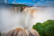 """Iguazu Falls, Iguazú Falls, Iguassu Falls or Iguaçu Falls are waterfalls of the Iguazu River on the border of the Argentine province of Misiones and the Brazilian state of Paraná. The falls divide the river into the upper and lower Iguazu. The Iguazu River rises near the city of Curitiba. The river flows through Brazil for most of its course, although most of the falls are on the Argentine side. Below its confluence with the San Antonio River, the Iguazu River forms the boundary between Argentina and Brazil.<br /> The name """"Iguazu"""" comes from the Guarani or Tupi words """"y"""", meaning """"water"""", and """"ûasú """", meaning """"big"""". Legend has it that a god planned to marry a beautiful woman named Naipí, who fled with her mortal lover Tarobá in a canoe. In rage, the god sliced the river, creating the waterfalls and condemning the lovers to an eternal fall. The first European to find the falls was the Spanish conquistador Álvar Núñez Cabeza de Vaca in 1541. About half of the river's flow falls into a long and narrow chasm called the Devil's Throat (Garganta del Diablo in Spanish or Garganta do Diabo in Portuguese). The Devil's Throat is U-shaped, 82 metres high, 150 m wide, and 700 m long. Placenames have been given also to many other smaller falls, such as San Martín Falls, Bossetti Falls and many others."""