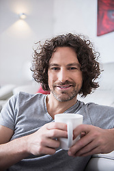 Man drinking cup of coffee at home, Munich, Bavaria, Germany