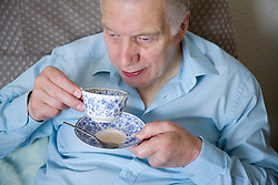 Older man sitting at home drinking a cup of tea,